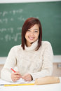 Happy young asian student in class sitting at her desk with the blackboard behind her giving the camera a beaming friendly smile Royalty Free Stock Images