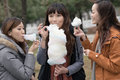 Happy young asian woman eating cotton candy with her friends women in outdoor Royalty Free Stock Photo