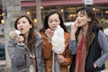 Happy young asian woman eating cotton candy with her friends women in outdoor Royalty Free Stock Image
