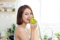 Happy Young Asian Woman Eating Green Apple on Kitchen. Diet. Die Royalty Free Stock Photo
