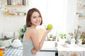 Happy Young Asian Woman Eating Green Apple on Kitchen. Diet. Royalty Free Stock Photo