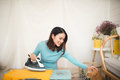 Happy young asian woman ironing clothes sitting on floor at home Royalty Free Stock Photo