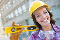 Happy young attractive female construction worker wearing hard hat and portrait of with level gloves protective goggles at Stock Photos