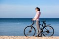 Happy young attractive woman on the bicycle trip relaxing beach sea in background Royalty Free Stock Photos