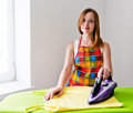 Happy young beautiful woman ironing clothes housework Royalty Free Stock Photo