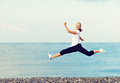 Happy young beautiful woman jumping at beach on the sea and rejoicing Royalty Free Stock Images