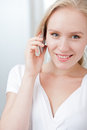 Happy young blond woman speaking on a cellphone Royalty Free Stock Photo