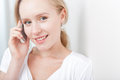 Happy young blond woman speaking on a cellphone Royalty Free Stock Images