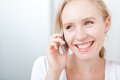 Happy young blond woman speaking on a cellphone Stock Images