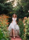 Happy young blonde girl in an elegant amazing long white wedding light dress with a long train, walking in a wonderful