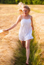 Happy young blonde girl in white dress with straw hat running th Royalty Free Stock Photo