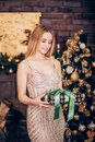 Happy young blonde woman in a Golden dress opening gift box near christmas tree Royalty Free Stock Photo
