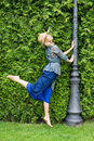 Happy young blonde woman walking barefoot on the green grass Royalty Free Stock Photo