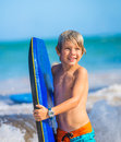 Happy young boy having fun at the beach on vacation with boogie board Stock Images