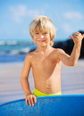 Happy young boy having fun at the beach on vacation with boogie board Royalty Free Stock Photos