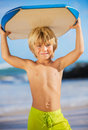 Happy young boy having fun at the beach on vacation with boogie board Royalty Free Stock Photography
