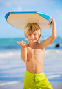 Happy young boy having fun at the beach on vacation with boogie board Royalty Free Stock Images