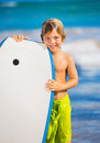 Happy young boy having fun at the beach on vacation with boogie board Stock Photo
