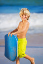 Happy young boy having fun at the beach on vacation with boogie board Royalty Free Stock Photo