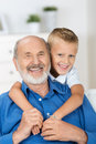 Happy young boy with his grandfather standing behind him arms around neck in a loving embrace Royalty Free Stock Images