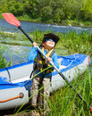 Happy young boy holding paddle near a kayak Royalty Free Stock Photo