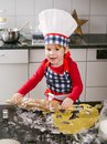 Happy young boy making cookies photo of an adorable in a chef hat and apron using a rolling pin and in the kitchen Stock Photography