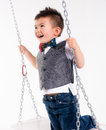 Happy young boy plays swing suspended moving laughing child play man has a blast back and forth Royalty Free Stock Photography