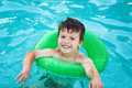 Happy young boy in pool with saver learning swim childhood Stock Photos