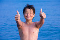 Happy young boy on the sea beach ok laughing of twelve showing thumbs up sign Stock Photos