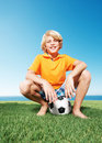 Happy young boy sitting on the football at park Stock Photos