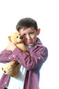 Happy young boy with teddy bear isolated over white background Stock Photography