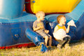 Happy young boys eating a large cotton candy ball sitting near colorful inflatable bouncer amusement Stock Images