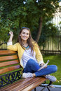 Happy young brunette sitting on a park bench Royalty Free Stock Photo