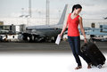 Happy young brunette woman walking with her travel bag and airline ticket in airport outside airport terminal and airplane Stock Image