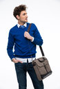 Happy young business man with bag looking away over gray background Stock Photography