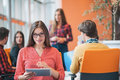 Happy young business woman with her staff, people group in background at modern bright office indoors Royalty Free Stock Photo