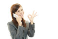 Happy young business woman making ok sign holding a mobile phone and talking Royalty Free Stock Images