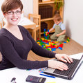 Happy young business woman working women on a laptop with her child playing at the back Stock Photo