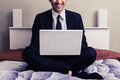 Happy young businessman sitting in bed with laptop Royalty Free Stock Photo