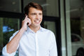 Happy young businessman talking on mobile phone near buiness center Royalty Free Stock Photo