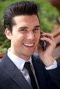 Happy young businessman talking on the phone outdoors close up portrait of a Stock Image
