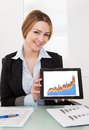 Happy young businesswoman presenting charts on digital tablet Royalty Free Stock Image