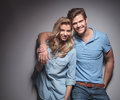 Happy young casual couple smiling for the camera against gray studio wall Royalty Free Stock Photography