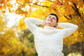 Happy young Caucasian handsome man staying in autumn park, stretching and touching head. Lazy autumn days. Royalty Free Stock Photo