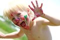 Happy young child with messy painted face a preschool aged is smiling at the camera while his is covered in paint Stock Images