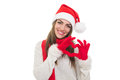 Happy young christmas woman showing heart with hands beautiful gesture wearing santa hat scarf and gloves smiling looking at Royalty Free Stock Image