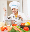 Happy young cook tests vegetarian food with ladle at commercial kitchen Royalty Free Stock Photo