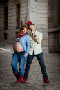 Happy young cool latin couple together outdoors with pregnant woman showing belly women and trendy men wearing casual Royalty Free Stock Image