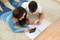 Happy young couple calculating invoice portrait of a lying on rug Royalty Free Stock Photography