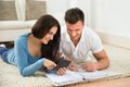 Happy young couple calculating invoice Royalty Free Stock Photo